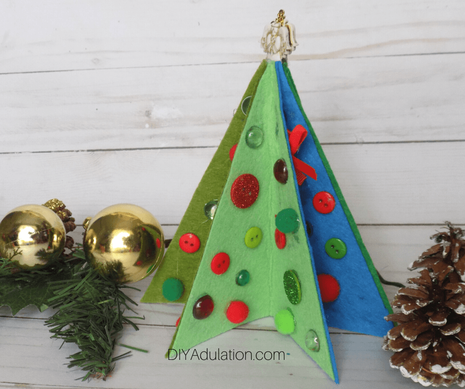 Decorated Felt Christmas Tree on Wood Background next to Greenery