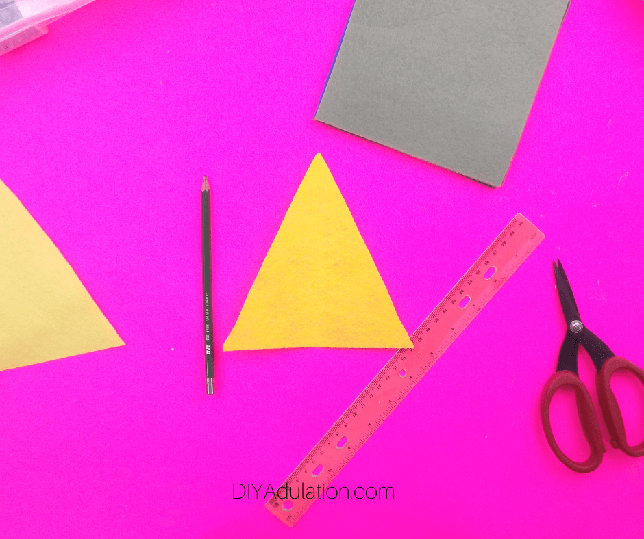 Felt Triangle next to Pencil and Scissors
