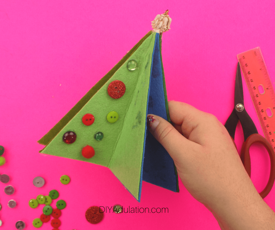 Hand Holding Partially Decorated Felt Christmas Tree