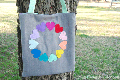 Gray tote bag with rainbow hearts in a circle design on the front