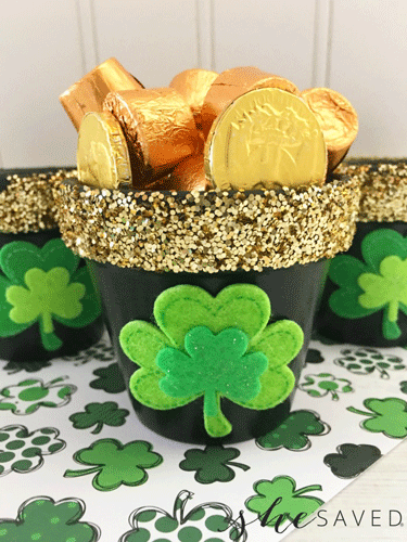 Black pots with gold glitter trim and green shamrocks filled with candy