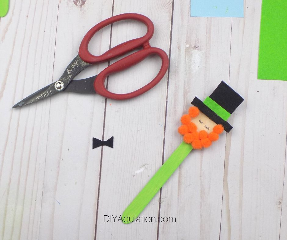 Small Black Felt Bow Tie next to Leprechaun Craft Spoon - DIY Adulation