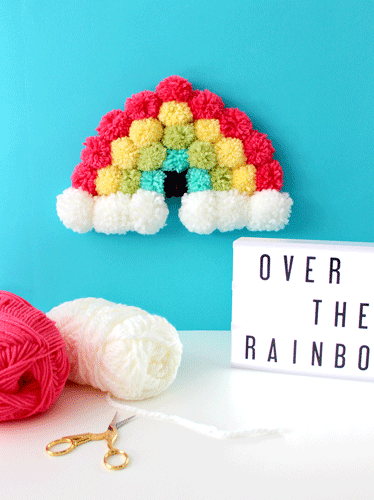 pompom rainbow on a teal wall with spools of yarn and decorative sign